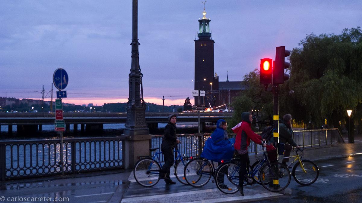 Ciclistas bajo la lluvia y Stadshus (ayuntamiento)
