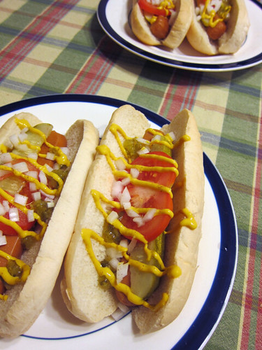 A plate with two big vegan hot dogs; they're stuffed with pickles, tomatoes, onions, relish, and mustard.