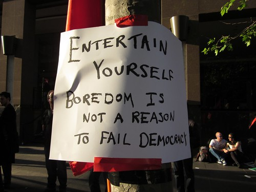 "A handwritten sign, posted on a tree reads: ""Entertain yourself. Boredom is not a reason to fail democracy."""