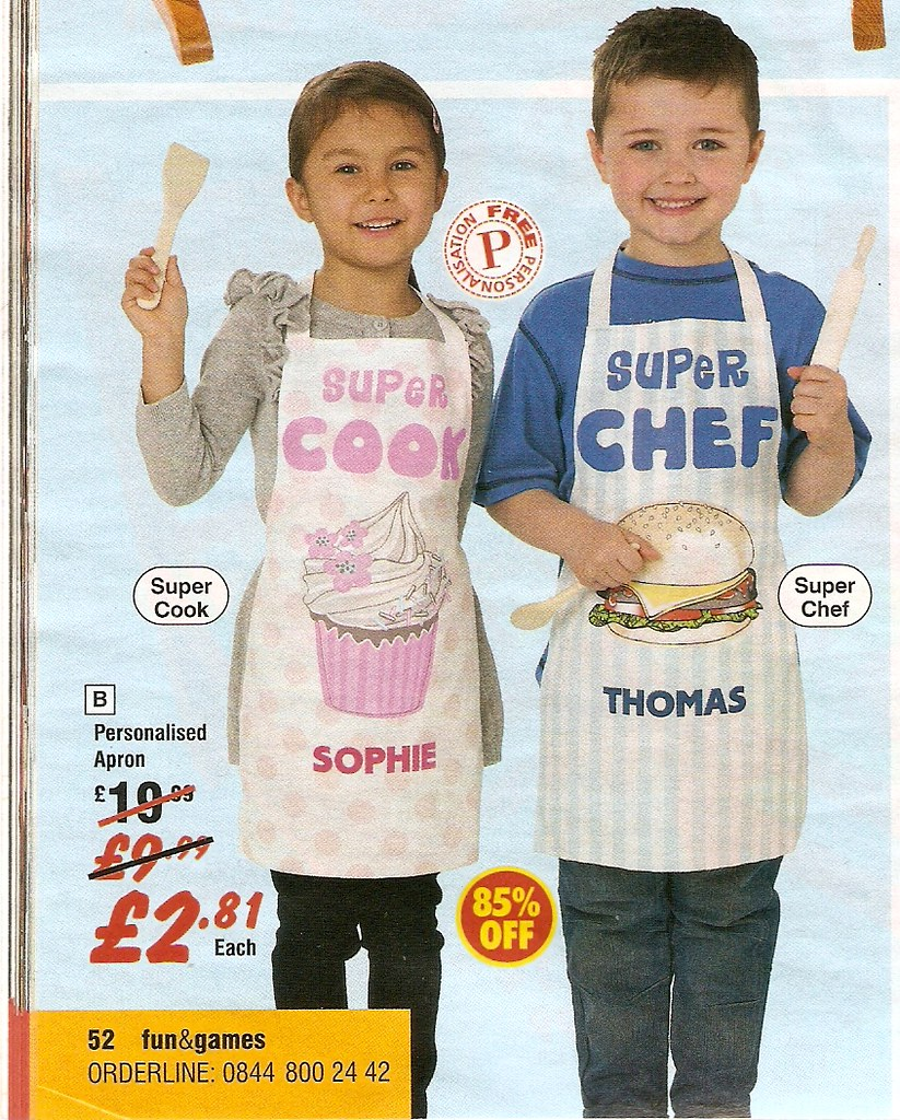 Catalogue image showing personalised aprons - a girl with pink-edged apron saying 'super cook' , a boy with blue-edged apron saying 'super chef'.