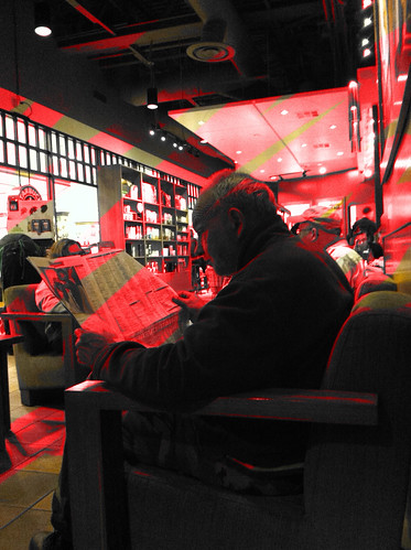 A man reads his paper at a full and noisy Starbucks