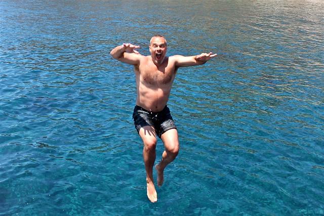 Marc saute dans l'eau, Santorin, Grèce