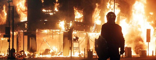 Riot police looks on as fire rages through a building in Tottenham, north London Sunday, Aug. 7, 2011. A demonstration against the death of a local man turned violent and cars and shops were set ablaze. (AP Photo/PA, Lewis Whyld)