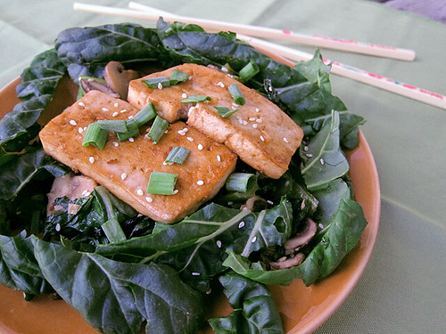 Plate of sauteed greens topped with two thick slices of tofu and surrounded by a circle of raw leaves. A pair of chopsticks sits off to the side of the plate.