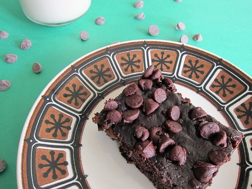 Photo of a rectangular brownie with chocolate chips on top. It's sitting on a small plate; in the background is a glass of almond milk and more chocolate chips sprinkled around the plate.