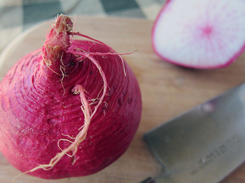Two vibrantly pink turnips, one intact and one cut in half.