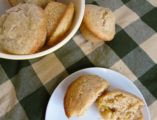 A bowl of muffins in the left-hand background and a plate with a muffin (cut in two) in the foreground.