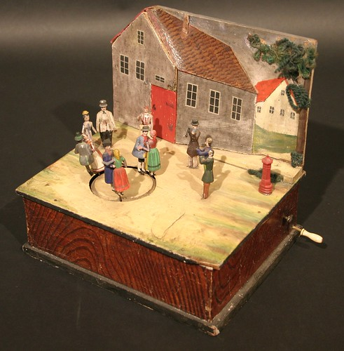 A 19th century Continental mechanical toy as a group of figures dancing before a house, which achieved £560
