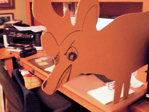 back side of a cardboard deer shaped target with funny angry face drawn on it