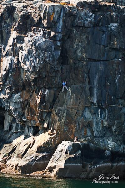 A climber ascends a cliff face on Cadillac Mountain.