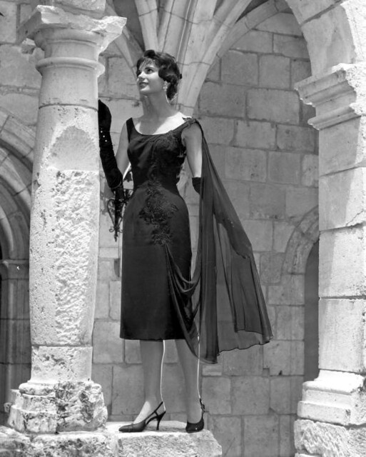 A fashion model in dress poses by column at Ancient Spanish Monastery: North Miami Beach, Florida