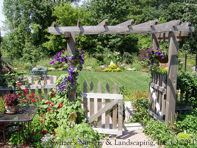 The cedar arbor at the top of the steps creates a beautiful frame of the lower flower garden.