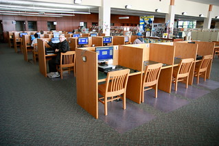 a picture of several rows of computers in a library.  some patrons are sitting scattered in the rows