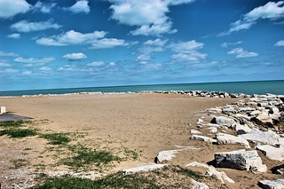 beach with blue sky, sand and rocks