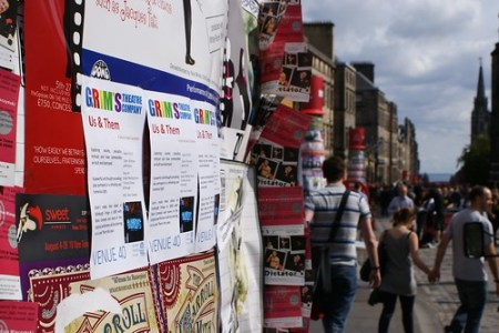 Image of a pillar covered in show flyers, with the Royal Mile in the background