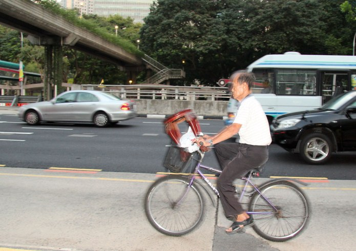 old man biking with stool on handlebars