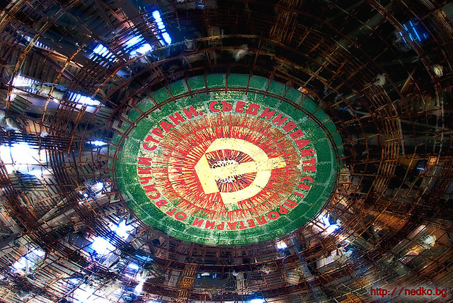 A proletarian motto and soviet symbol under the roof of an old bulgarian communist monument at Buzludzha