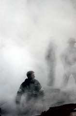 A fire fighter emerges from the smoke and debris of the World Trade Center, by Jim Watson