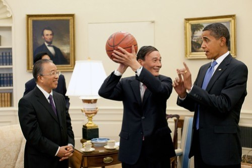 Chinese Vice Premier Wang Qishan, center, holds the basketball given to him by President Barack Obama