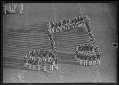 Harvard band forming music notes on field, Har...
