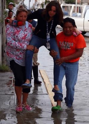 Repórter é carregada para não molhar os pés durante cobertura de enchente