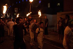 Volunteers torch bearers lead capoeira performers.