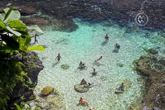 People swim in the turquoise waters of Uluwatu.