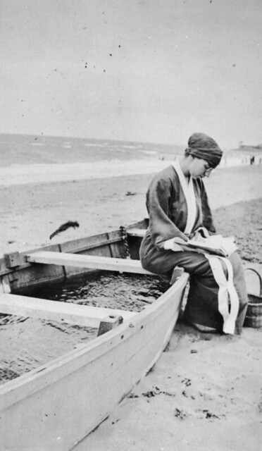 Woman sitting on a beached boat reading a book, ca. 1925