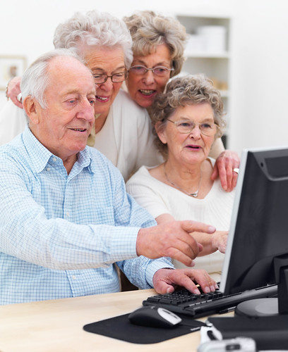 Elderly people working together on computer