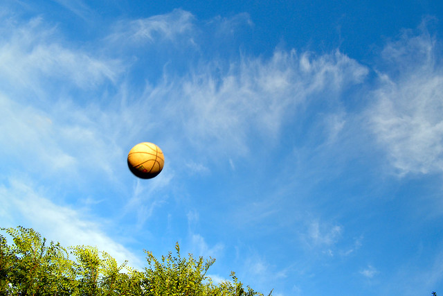 A photo that freezes or isolates the motion of an object - Basketball against the late afternoon sky