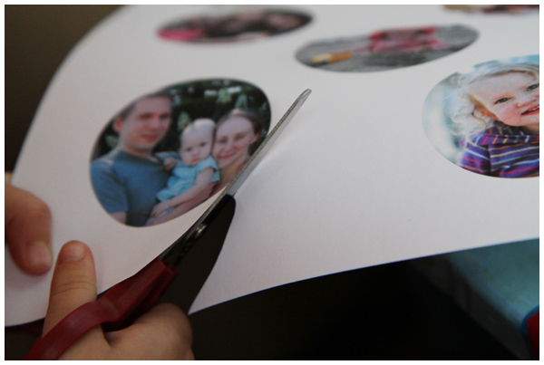 Kid using scissors to cut out circular family photos