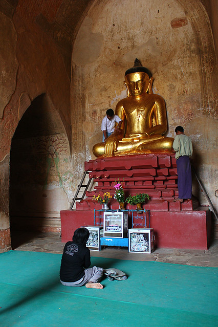 Devotees applying gold leaves to a Buddha statue, Bagan
