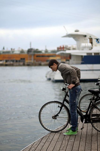 A man with a bicycle peering off the dock, Barcelona, Spain