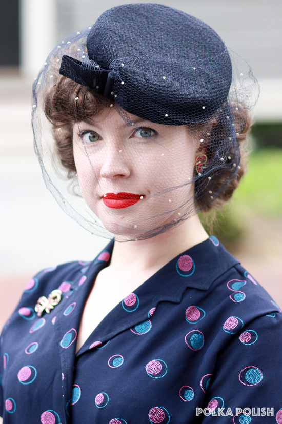 A small navy tilt hat is the perfect finishing touch to a 1940s daywear outfit