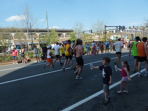 Little kids giving out bottles of water to marathon runners at the Boston Marathon 2012
