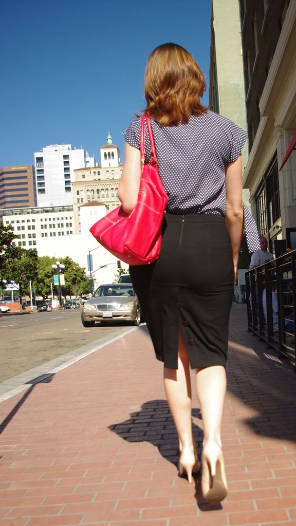 Lady carrying a bright red purse on a downtown sidewalk