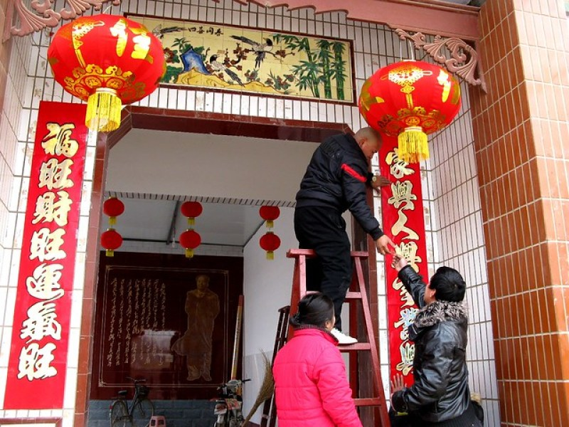 Putting up door decorations / 贴春联