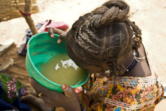 Aldaoula Banounassane, 20, drinks dirty water to quench her thirst. She is hot and exhausted having walked for three days from Mali to find the refugee camp in Yassan, Niger. Photo: Fatoumata Diabate/Oxfam