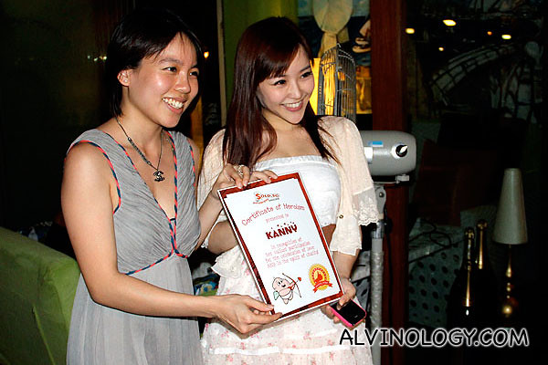 "Blogger and actress, Kanny, being presented with a ""certificate of bravery"" from SOLD.sg"