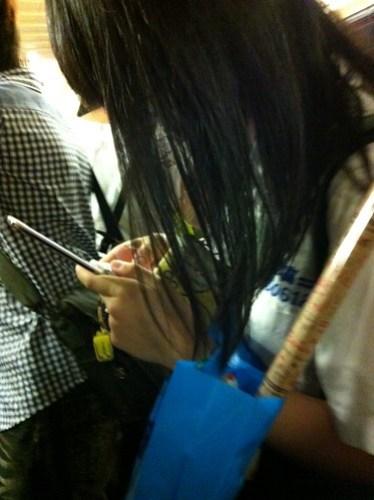 一個學生,專注地看著手機,傳著訊息。