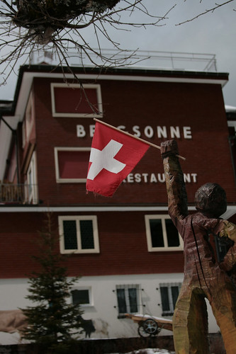 a wooden Swiss-flag-wielding statuette greets hikers along the way to Rigi Kulm