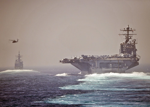 The aircraft carrier USS Abraham Lincoln (CVN 72), left, and the guided-missile cruiser USS Cape St. George (CG 71) transit the Strait of Hormuz.