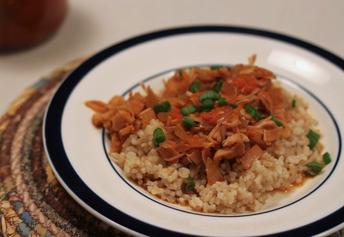 White plate with short-grain brown rice topped with a mystery dish!