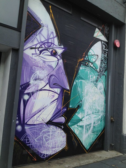 Graffiti artwork of purple and green angular faces, Valencia Street