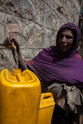 Happy woman farmer fetchs water from a tap water