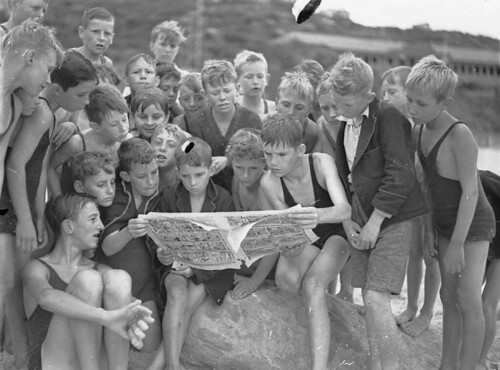 Boys reading the comics from the Sunday papers