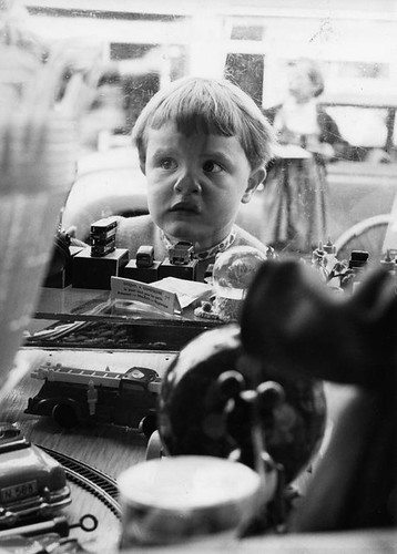 Kind bij etalage speelgoedwinkel / Child at the shop-window of a toy shop by Nationaal Archief