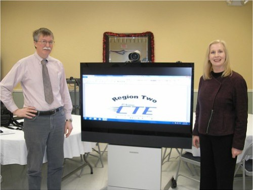 Region II School of Applied Technology Director Michael Howard and Maine's USDA Rural Development State Director, Virginia Manuel, poses in front of distance-learning technology.
