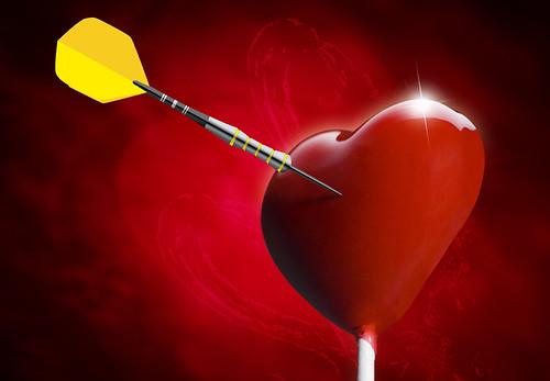 Heart-shaped lollipop hit by an arrow