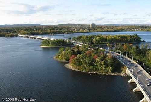Aerial shot of the Champlain Bridge which crosses the Ottawa River from Ottawa, Ontario to Gatineau, Québec. The bridge traverses several islands. Ontario is on the near shore and Québec is on the far shore.
